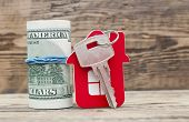 House keys over the hundred dollar banknotes against wooden background