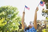 Low angle view of a young girl holding up two American flags at the park