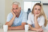 Fed up couple sitting at the counter at home in the kitchen