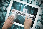 Hand touching the word confidential on search bar on tablet screen on crumpled papers