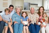 stock photo of three sisters  - Portrait of smiling multigeneration family spending leisure time together at home - JPG