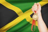 Medal In Hand With Flag On Background - Jamaica