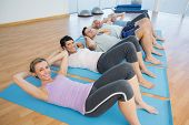 foto of senior class  - Side view portrait of fitness class lying on mats in row at yoga class - JPG