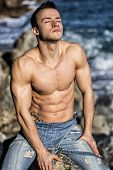 Muscular Young Man Sunbathing On Rock By The Sea Or Ocean