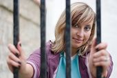 cute girl is looking through the bars