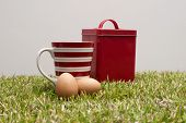 Red tin, coffee cup and two eggs.