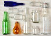 High angle shot of assorted glass bottles on a whitewashed wooden table. Clear Glass, Blue and Green