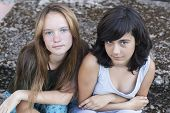 Two young beautiful teen girls sitting on a stone background