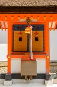 Japanese temple bell and the donation box in front of the altarin Fushimi Inari Taisha Shrine, Kyoto, Japan.