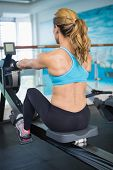 Rear view of a young woman working on fitness machine at the gym