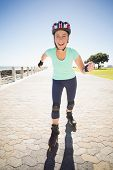 Fit mature woman rollerblading on the pier on a sunny day