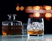 stock photo of whiskey  - glass with whiskey and ice on a glass table - JPG