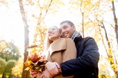 love, relationship, family and people concept - smiling couple with bunch of leaves hugging in autum