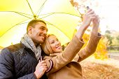 love, relationship, family, technology and people concept - smiling couple making selfie in autumn p