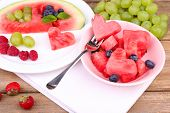 Fresh juicy watermelon slice  with cut out heart shape, filled fresh berries, on plate, on wooden ba
