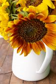 Beautiful sunflowers in pitcher on wooden background