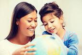 family, children, education, school and happy people concept - mother and daughter with globe