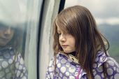 Sad Little Girl Leaning Against A Window