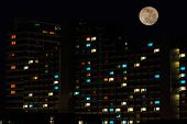 Full Moon Over Colorful Windows Of Residential House