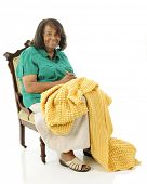 A senior woman happily crocheting her almost-finished afghan.  On a white background.