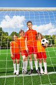 Kids stand in line with football behind woodwork
