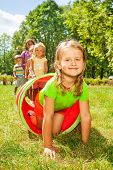 Happy girl crawl through play tube with friends