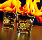Two Glasses Of Whiskey With Ice Cubes In Front Of The Flame