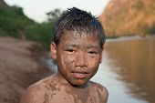 stock photo of ou  - Boy of Asia with sand in the face at Nam Ou River in Laos - JPG