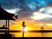 picture of gazebo  - Silhouette of young woman practising yoga meditation in standing full lotus position near gazebo or pagoda at beach in Bali during sunrise or sunset with her dog - JPG