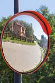 picture of emaciated  - reflection in the mirror of the road from a stone blocks at the house green grass and forest - JPG