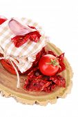 Sun dried tomatoes in glass jar and basil leaves isolated on white