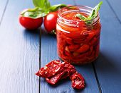Sun dried tomatoes in glass jar on color wooden background