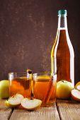 bottle of apple vinegar with fresh apples on wooden table