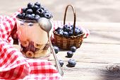 Natural yogurt with fresh blueberries on wooden table