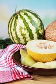 Melon and watermelon on brown plate on bamboo plate on napkin on grass on natural background