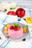Heart shaped cake with fruits and berries on plate on tablecloth