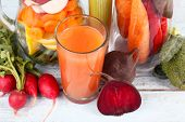 Jar of cut vegetables and glass of fresh carrot juice with vegetables on wooden table