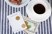 Check, cup of coffee and money on table close-up