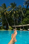 Close-up of female foot in the blue water on the tropical pool. Vacation holidays.