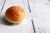 Tasty bun with sesame on color wooden background
