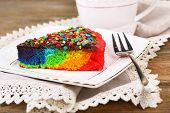 Delicious rainbow cake on plate and cup with hot drink, on wooden background