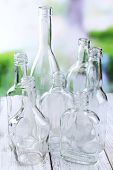 Empty glass bottles on table on bright background