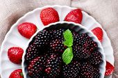 Bowl of blackberries and plate of strawberries on sacking background