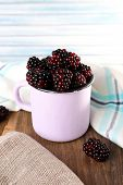 Metal mug of blackberries on napkin on wooden table on light background