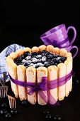 Tasty cake Charlotte with blueberries on black wooden table