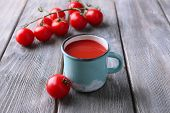 Homemade tomato juice in color mug and fresh tomatoes on wooden background