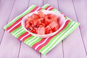 Slices of watermelon in pink plate on napkin on wooden background