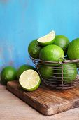 Fresh juicy limes in basket on blue wooden background