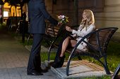 picture of fiance  - Man with flowers for woman at night - JPG