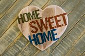 Home Sweet Home Message Wooden Heart On Light Green Painted Background
